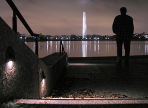 Man viewing monument at night